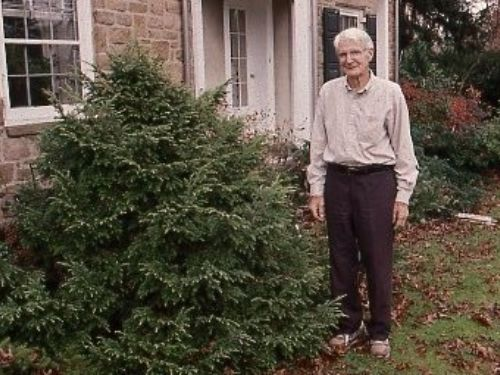a historic photo of Frank Heckman with the original 'Betty Rose' planted in front of his home in Pennsylvania.
