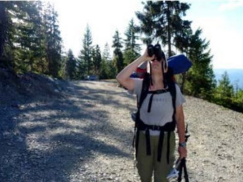 Leah Alcyon looking at conifers with binoculars at the parking lot of Devil's Punchbowl in the Siskiyou Wilderness Area, California