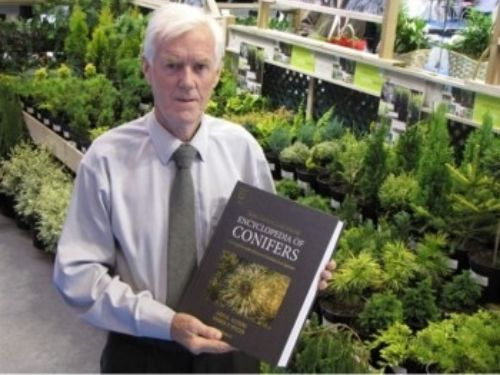 Derek Spicer holds Volume II of the RHS Encyclopedia of Conifers